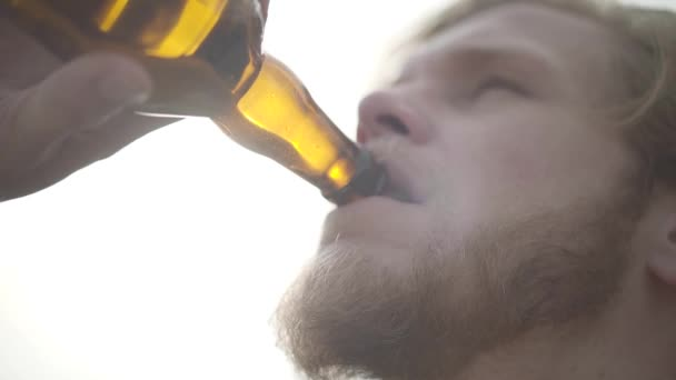 Close up face attractive bearded man drinking beer and enjoying beverage outdoors. Guy tastes lager from bottle looking at the camera. Slow motion.