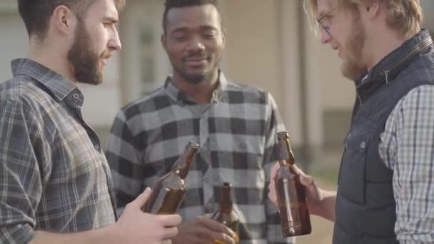 Portré három kaukázusi és afro-amerikai férfi állt a kertben sört iszik. A férfiak Clink a palackok mosolyogva. Régi barátok szórakozni együtt