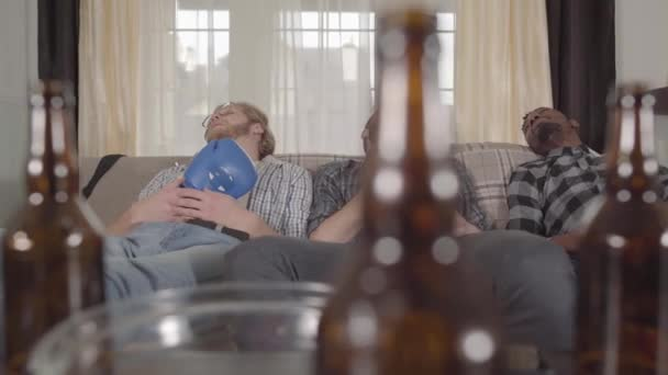 Two caucasian and one african american men sleeping on the sofa after watching boxing on TV. Empty beer bottles and chips bowl are on the table.