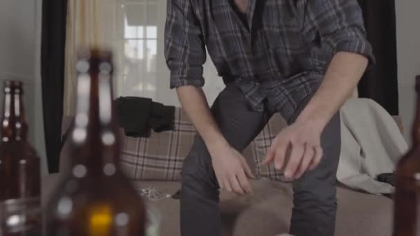 Young bearded man gets up from the sofa and walks away, grabbing his cellphone and headphones. Blurred empty beer bottles and chips bowl are on the table.