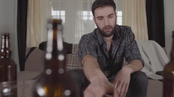 Young bearded man sitting on the sofa takes remote and turned on the TV. The guy feels bad, he rubs his face. Blurred empty beer bottles on the table. The morning after hangover. Unhealthy lifestyle