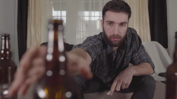 Young bearded man sitting on the sofa takes empty beer bottle from the table and look at it with perplexity. The guy feels bad after hangover. Unhealthy lifestyle