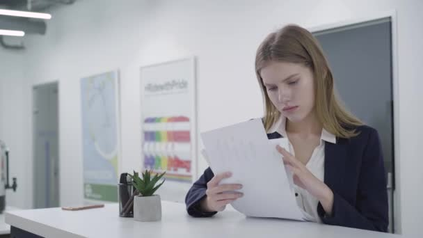 Concerned thoughtful young lady in formal clothes attentively checking papers in the office standing at the counter. Woman with long hair is upset, she is trying to solve problem. Camera moves right
