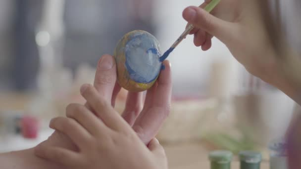 Woman hand holding Easter egg while little girl clumsily painting on it a heart with a small brush close up. Creative work. Preparation for the Easter holiday. Mother and daughter have fun together