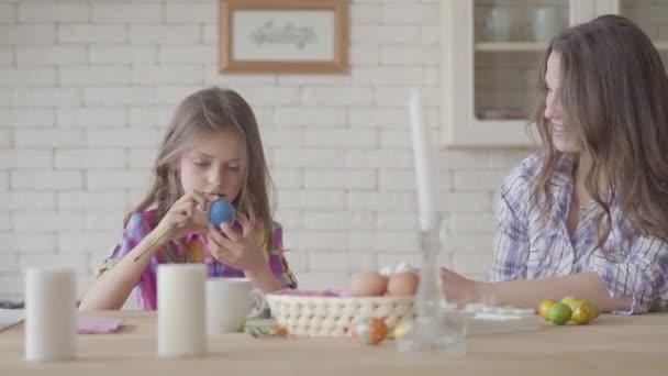 Porträt hübsche Mutter und süße Tochter am Ostertisch. Nettes Mädchen bemalt ein Osterei mit einer dünnen Quaste. Beziehung Mütter und Töchter. eine glückliche Familie. Vorbereitung auf das Osterfest.