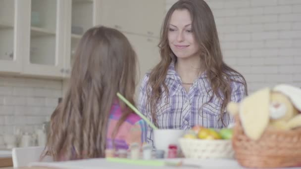 Young mother and cute girl chatting on the kitchen. The kid touches mothers face with her small hands. Friendly relationship between mom and daughter. A happy family.