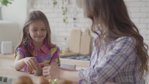 Portrait mother and cute daughter sitting at the Easter table. Little girl paints an Easter egg with a thin tassel. Relationship mothers and daughters. A happy family. Preparation of the Easter.
