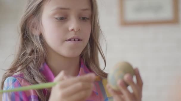Portrait of cute girl with long hair painting Easter egg using a brush sitting in the kitchen close up. Preparation for the Easter holiday. Concept of creativity