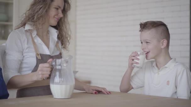 A fiú iszik tejet ülve az asztalra mellett az anyja és testvére a konyhában. Testvériség. Családi kapcsolat.