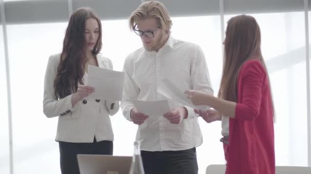 Handsome businessman in glasses discussing documents with two female colleagues standing in front of large window in a light comfortable office. Two girls in formal wear communicating with a boss