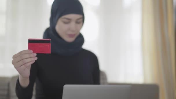 Portarait mladé krásné muslimské ženy, která bude platit za něco s kreditními kartami v internetovém obchodě s notebookem, zavřít