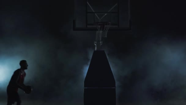 Young man in red uniform throws the ball in the basket on the dark background in the cloud of smoke and walks away. Professional basketball game player in action. Concept of sport