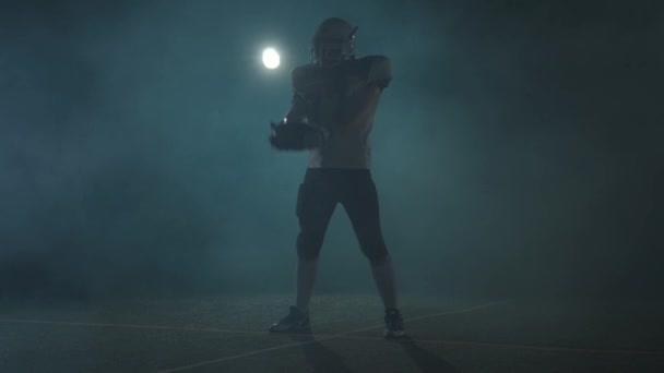 Hráč amerického fotbalového sportovce v fotbalové helmě stojící na poli na černém pozadí v oblaku kouře s koulí v ruce. Muž, který zvedá míč, dělá vyvolávání gest