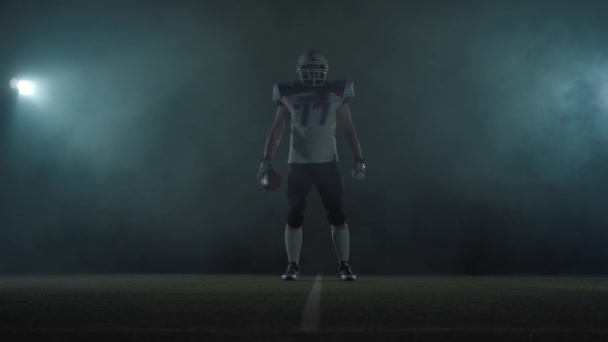 Hráč amerického fotbalového sportovce v fotbalové helmě stojící na poli na černém pozadí v oblaku kouře s koulí v ruce. Muž zvedující míč dělá výhružné gesta