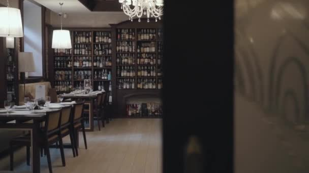 Cozy hall of a beautiful expensive restaurant. Exquisite interior of a cafe or pub. Shelves with different varieties of whiskey.