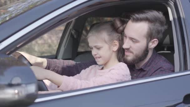 Little girl sitting on fathers lap in the car holding wheel close up. The child is learning to drive the car. Smiling man spending time with his daughter. Family leisure. Camera moving right