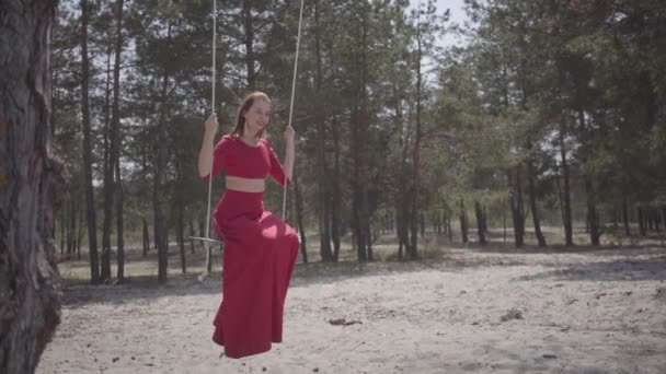Close up portrait of graceful beautiful young woman in red dress sitting on the swing in the forest and looking an amazing spectacular view. Slow motion.