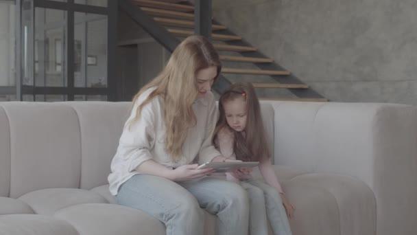 Portrét krásná mladá matka a její roztomilá dceruška používají tabletu a usmívají se, sedí na pohovce ve velkém domě. Rodinné vztahy.