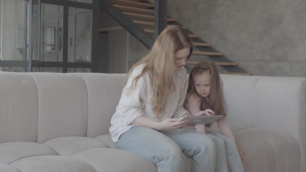 Na portrétu je hezká mladá matka a její roztomilá dceruška používá tabletu a usmívá se, sedí na pohovce ve velkém domě. Rodinné vztahy.