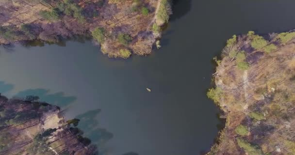Aerial shot of the small boat in the middle of a beautiful wide reflective river. Active lifestyle, connection with nature. Drone shooting, top view. Camera moving down lower