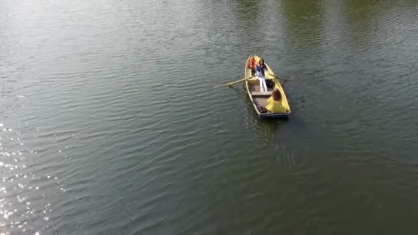 Two young pretty girls are boating in the small boat in the middle of beautiful reflective lake or river. One woman is paddling. Active lifestyle. Drone shooting, top view, aerial shooting