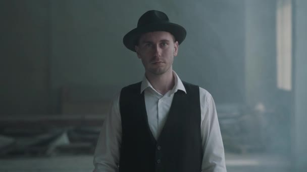 Portrait handsome confident man in a hat looking to the camera in an abandoned building. Boss of the mafia is in an empty building. Slow motion.
