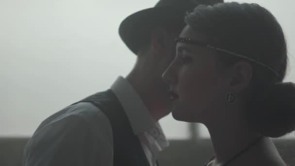 Porträt stattlichen selbstbewussten Mann in einem Hut flüstern Witz auf dem Ohr der eleganten Dame, sie lacht. Der Kopf der Mafia mit seiner jungen lieben Frau. Kriminalpolizei, coole Kerle, Mafia