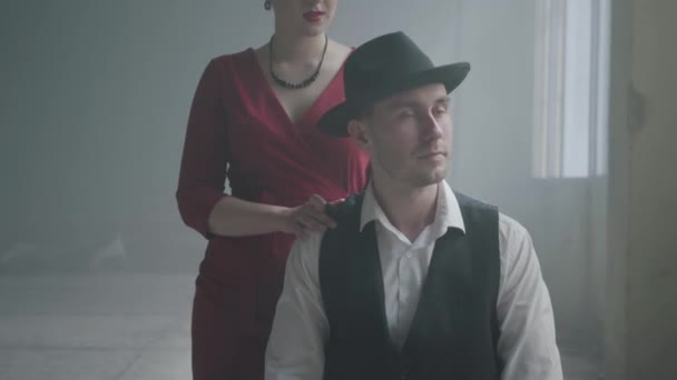 Handsome confident mafia boss in a hat and a vest sitting in an abandoned building. The elegant woman in red dress coming from behind and hugging the man smiling. Happy couple of gangsters