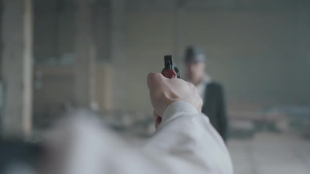 The hand of an unrecognizable man aiming a gun, blurred figure of a confident man in the suit and hat in front of him. The guy is going to kill his enemy. Mafia disassembly