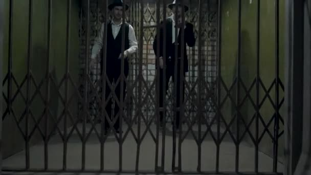 Two gangsters men in formal suits and fedora hat opening a metal forged  gates