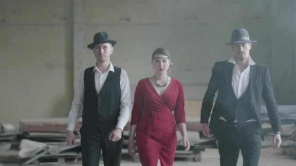 Two confident men in hats and suits and woman in red dress walking toward the camera in an abandoned building. The mafia in an empty building. Cool guys, thug, mafia, criminal gang