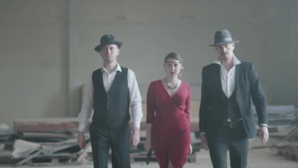 Porträt zweier selbstbewusster, gut gekleideter Männer, die in einem verlassenen Gebäude neben einer Frau in rotem Kleid stehen und mit einer Pistole auf die Kamera zielen. Coole Typen, Schläger, Mafia, Verbrecherbande
