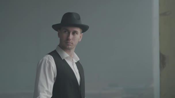 Portrét pohledného muže v klobouku, který hledí do kamery v opuštěné budově. Šéf mafie je v prázdné budově. Na portrét zločinného orgánu. Sebevědomý podnikatel relaxující.
