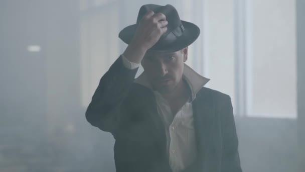 Porträt eines erfolgreichen Gentleman in einem klassischen altmodischen Anzug, der einen Hut hält und selbstbewusst in die Kamera schaut. Porträt der Kriminalpolizei. Selbstbewusster Geschäftsmann entspannt