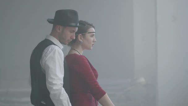 Elegante junge Frau im roten Kleid, die langsam auf eine Pistole zielt, steht ein hübscher galanter Mann dahinter, richtet ihre Hand, Seitenansicht. Glückliches Paar Gangster. Bonnie und Clyde. seitenansicht