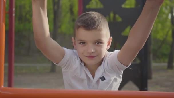 Portrét malého hezkého chlapce šplhání po hřišti na hřiště. Aktivní životní styl, bezstarostný dětství, rozkošný chlapec hrající venku