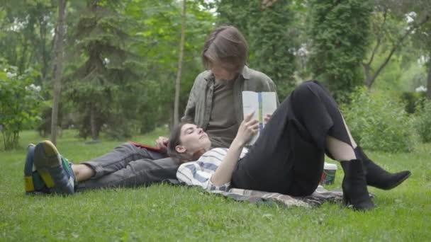 Fiatal pár alkalmi ruhában együtt töltik az időt a szabadban, randiznak. A fickó, aki a takarón ül a füvön, egy csinos lány fekszik az ölében, és újságot olvas. Nyári szabadidő