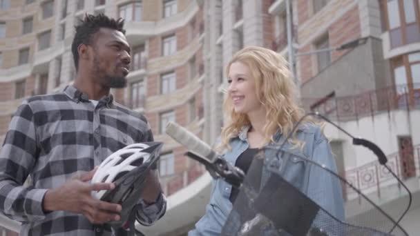 Portrét důvěrného a hezkého afrického Američana s bicykly na pozadí městské architektury hovotuje s atraktivní ženou. Dva kamarádi si povídali venku. Mezinárodní