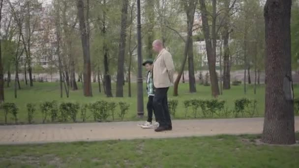 Adorable grandfather and cute little grandson walking in the park together. Generations concept. Friendly family. Leisure outdoors.