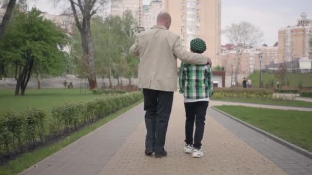 Back view of grandfather and grandson walking in the park with their backs to camera. The man hugs the child by his shoulders. Generations concept, Summertime leisure