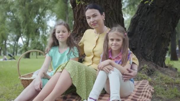Dospělá žena, která sedí na trávě pod stromem v parku se dvěma roztomilým dědečkám, dívá se do kamery a usmívá se. Šťastný rodinný čas v přírodě