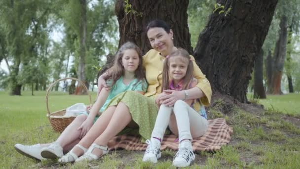 Family, leisure and people concept. Happy grandmother and granddaughters having picnic at summer park. Mature woman sitting on the grass under the tree in the park with two granddaughters outdoors.