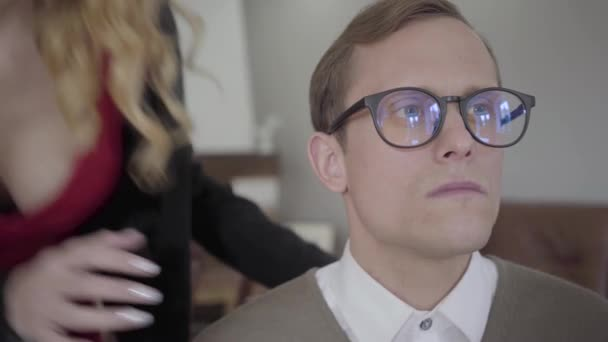 Blond sensual woman suddenly kissing the cheek of modestly dressed man in  glasses  The nerd surprised, confused and shocked, he is shy  Beautiful  lady flirting with the guy
