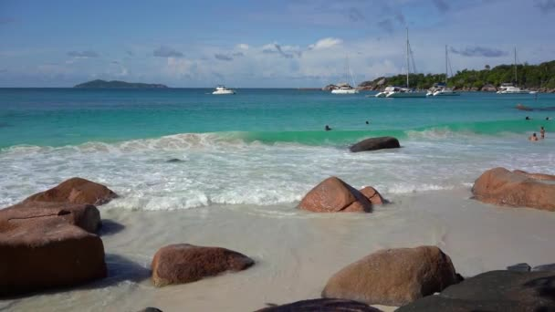 Seychelles. Praslin Island. Beautiful view of the stony coast of the island located in the Indian Ocean. Private yacht in the blue sea water on the background. People bathe in the sea.