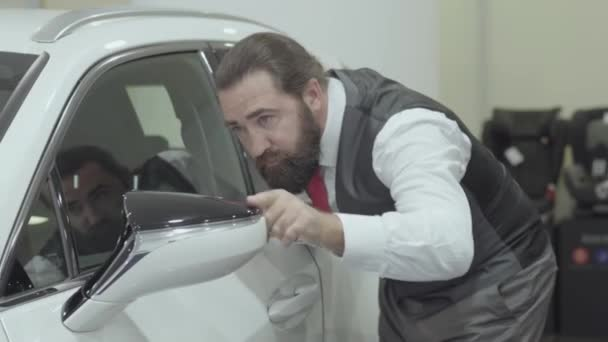 Portrait attractive cute confident bearded businessman in a business suit inspects newly purchased auto from the car dealership. Car showroom. Advertising concept.