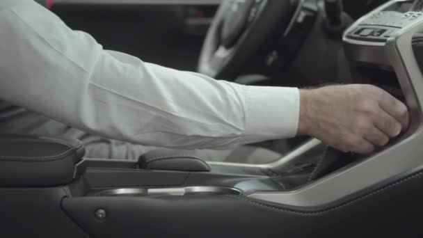 Unrecognized successful man sitting in the vehicle and inspects newly purchased auto from the car dealership. Car showroom. Advertising concept.