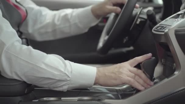 Unrecognized successful businessman sitting in the vehicle and inspects newly purchased auto from the car dealership. Car showroom. Advertising concept.