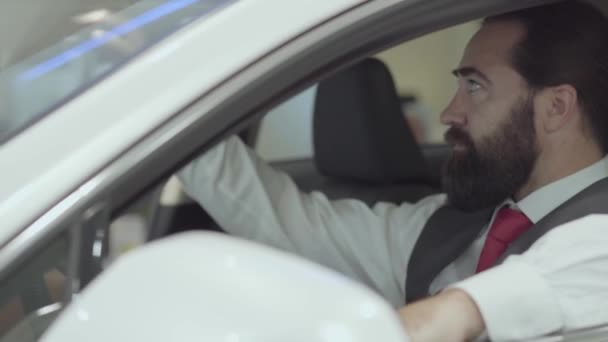 Portrait attractive confident bearded businessman sitting in the vehicle and inspects newly purchased auto from the car dealership. Car showroom. Advertising concept.