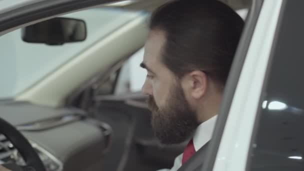Portrait attractive cute confident bearded businessman sitting in the vehicle and inspects newly purchased auto from the car dealership. Car showroom. Advertising concept.