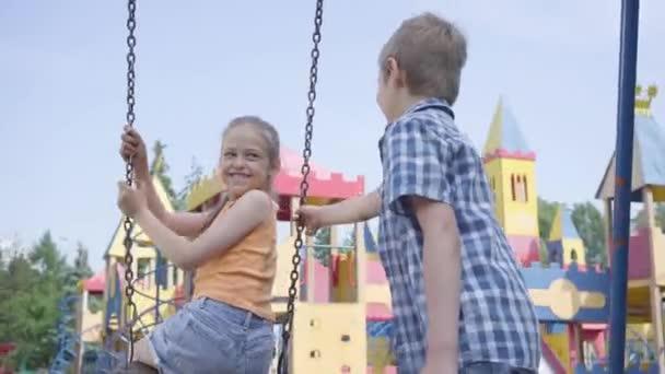 Roztomilý kluk houpal se s dlouhými vlasy na houpačce s úsměvem. Pár šťastných dětí venku. Zvláštní bezstarostní děti v lásce venku.